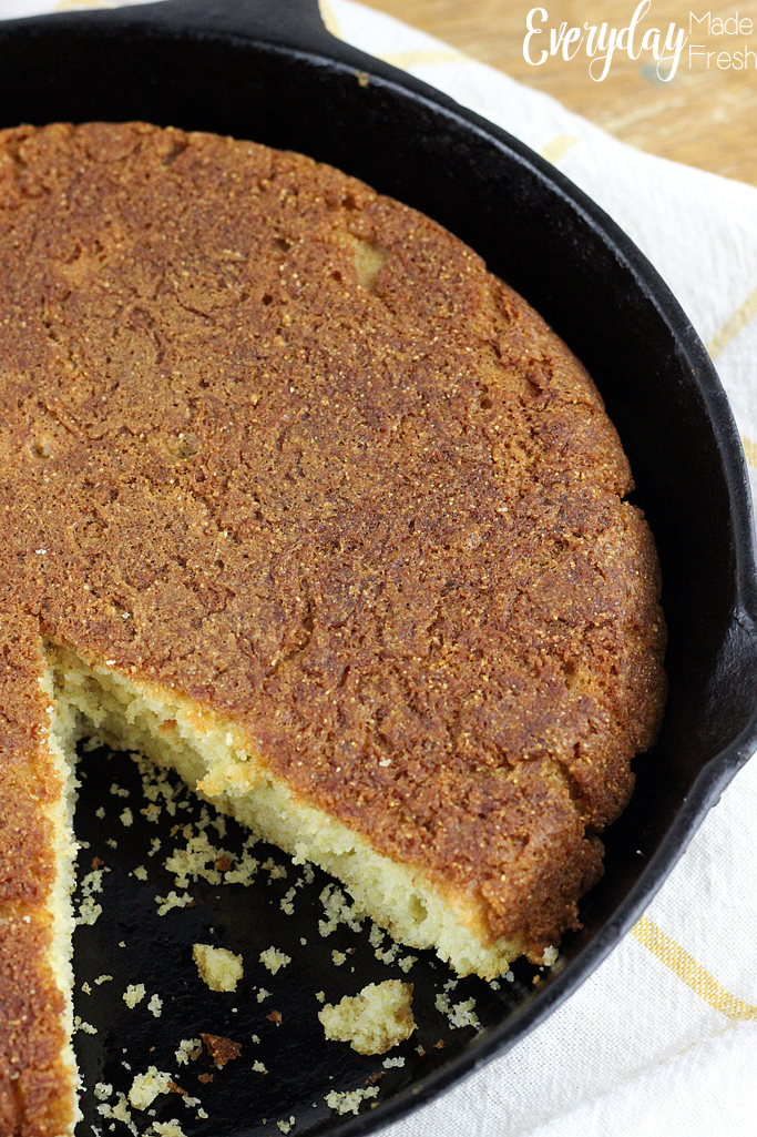 a pan of corn bread in a cast iron skillet, with one slice missing.