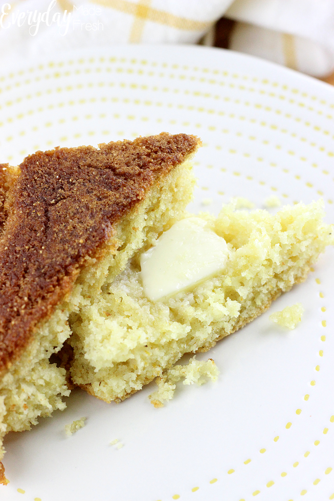 Up close slice of corn bread on a plate. It's been halved and a slab of butter is melting into the corn bread crumbles.