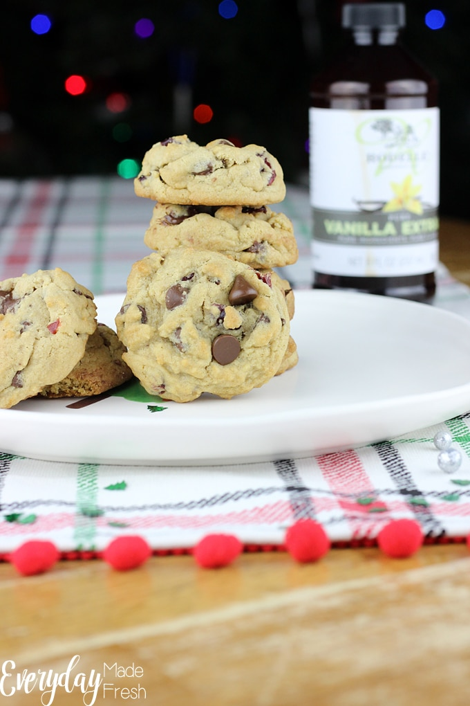 plate of cranberry chocolate chip cookies, vanilla extract off to the side, behind the plate. christmas lights blurred in the back ground.