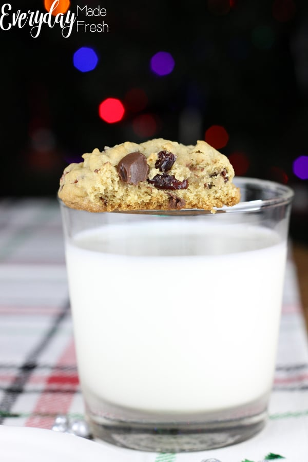 a cranberry chocolate chip cookie with a bite mark, balanced on the rim of a glass of milk
