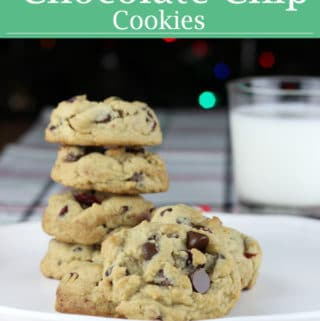 a plate of thick cranberry and chocolate chip cookies, stacked, with a glass of milk.