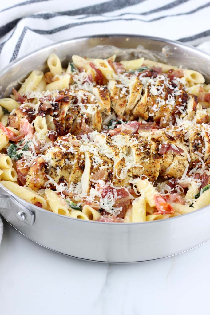 Easy Chicken & Bacon Pasta with Spinach and Tomatoes is quick and delicious. Seasoned chicken, crispy bacon, fresh spinach and tomatoes take this weeknight recipe to the next level!
