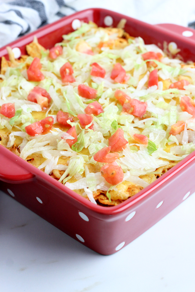 Baked Taco Salad Casserole is simple and delicious - Packed with layers of seasoned ground beef, refried beans, nacho cheese chips and cheddar cheese. You're family will love this on your next taco night.