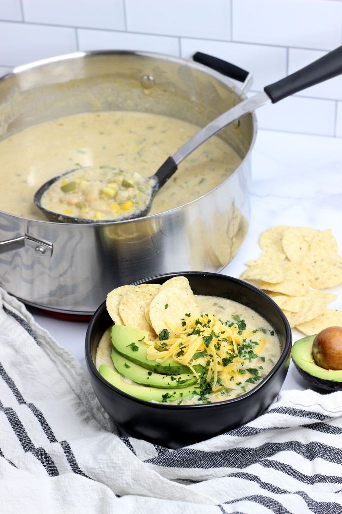 A pot and a bowl of enchilada soup, with toppings. Sliced avocado, shredded cheese, tortilla chips and cilantro.